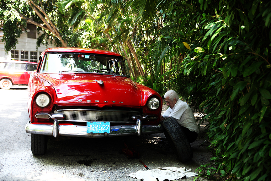A man changes the spare tire on his Chrysler Desoto outside the Hitchcock House in Havana, Cuba on June 12.