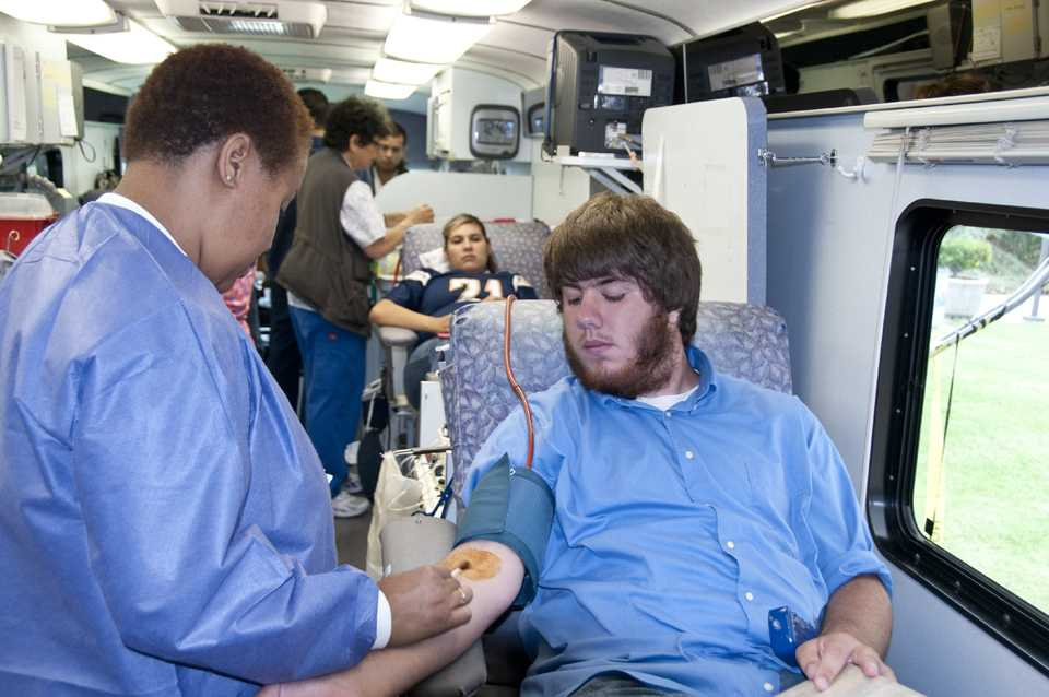 Blood Collection Specialist Denise Green prepares Dominic Shoopmann for donation at Sept. 11 blood drive.
