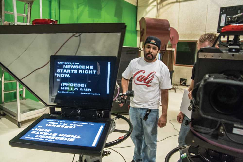 Mario Moran, a Newscene teammember, prepares the camera teleprompter for an upcoming broadcast in City's television studio, Sept. 28.   Troy Orem, City Times