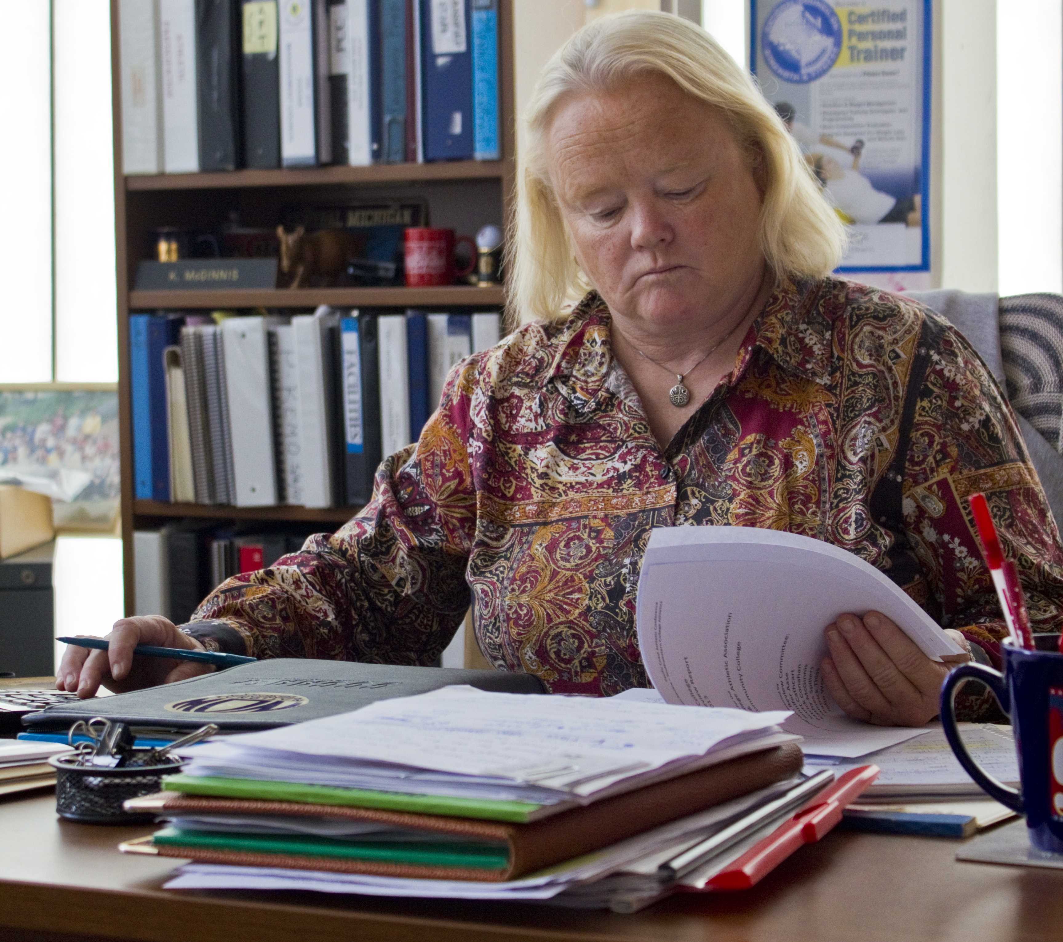 Kathy McGinnis works on paperwork for the upcoming fall season. Mary Watson, City Times