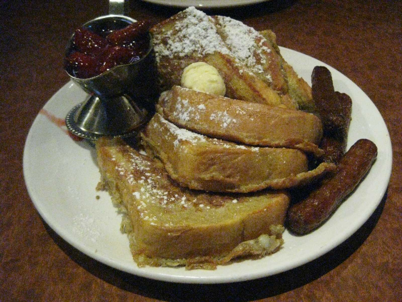 French toast with a side of strawberry sauce and sausage. The Broken Yolk Cafe serves generous portions. Michelle Moran, City Times.