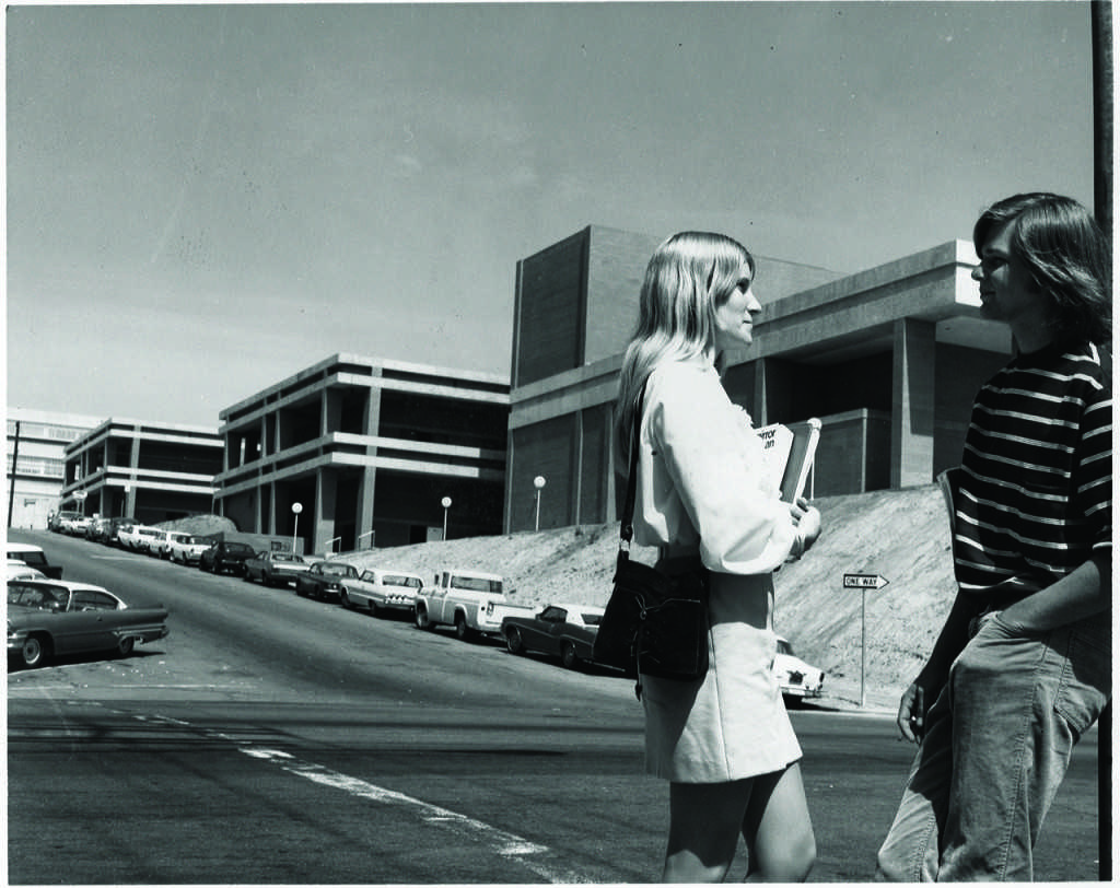 Two students stand across the street from City College's new theater in the 1970s. The complex, located on C Street, is now known as the Saville Theatre. Photo courtesy of the City Times archive.