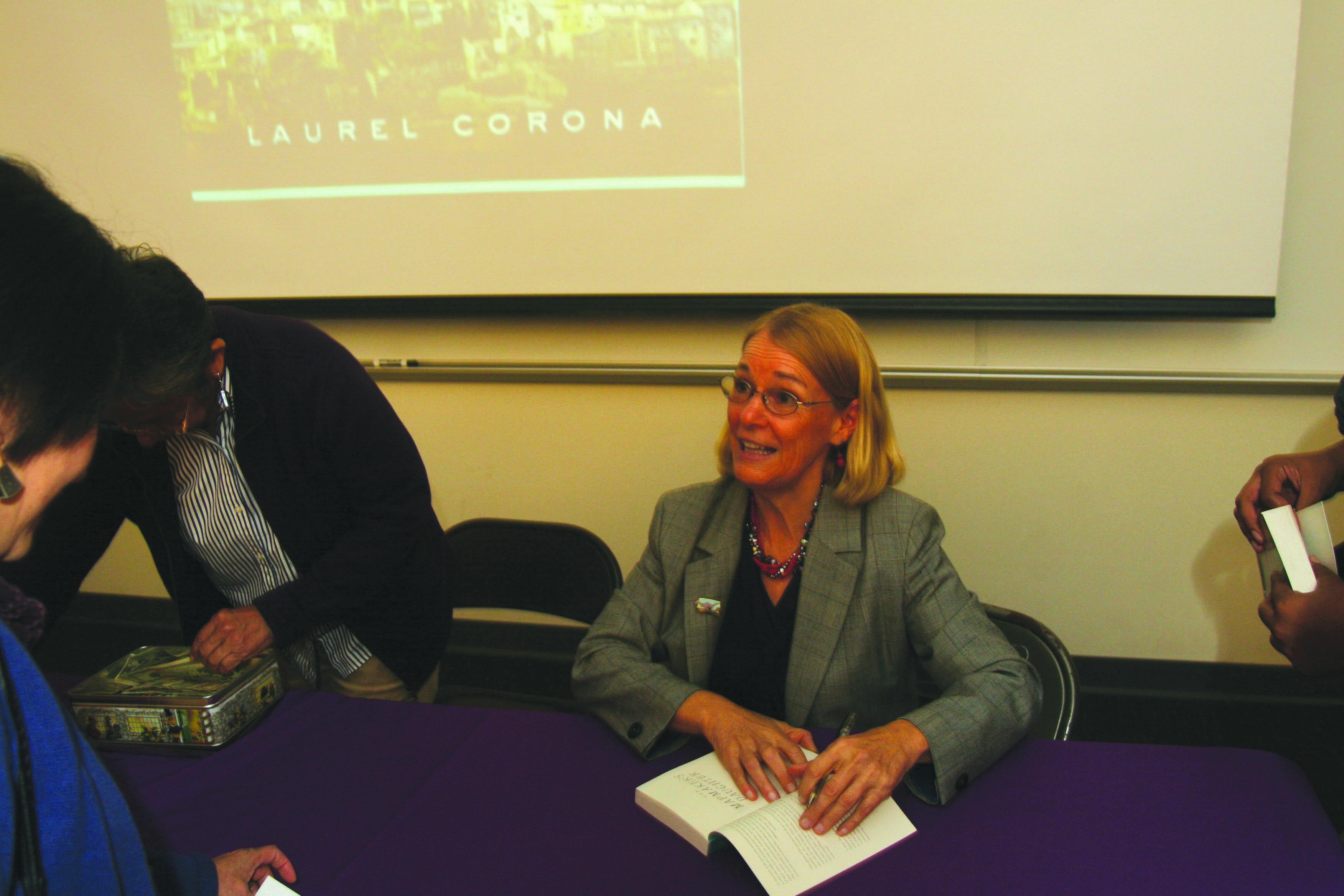 Humanities professor Laurel Corona with a copy of her latest book