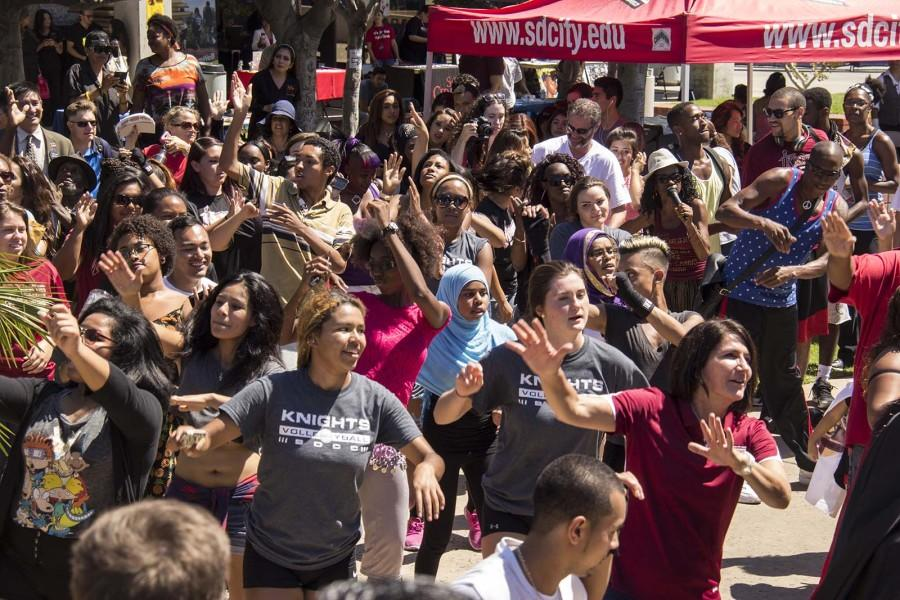 City College students dance the Centennial Shuffle, a dance created for the centennial by Spirit Day master of ceremonies Ruby Wilson, in Gorton Quad.