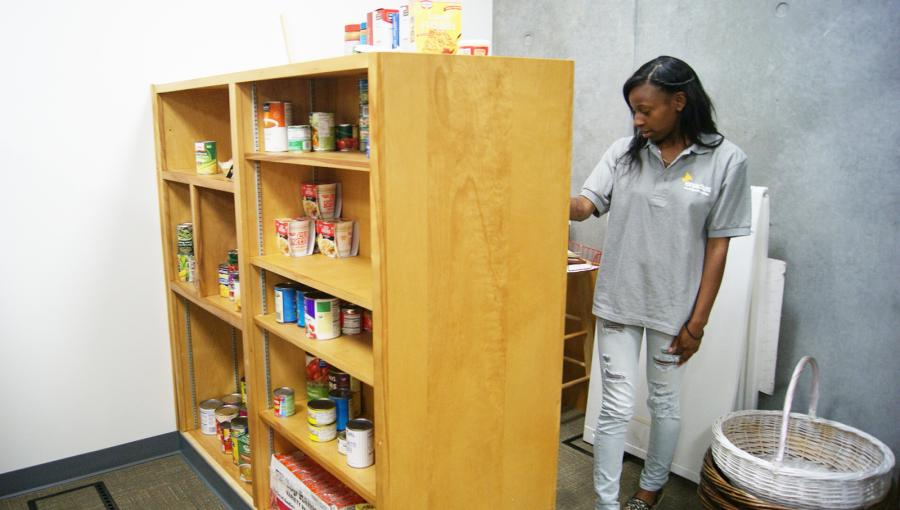 Bridgette Babers, a student involved in the Small Business Entrepreneur Program, restocks food in the pantry. Photo credit: Lydia Grijalva