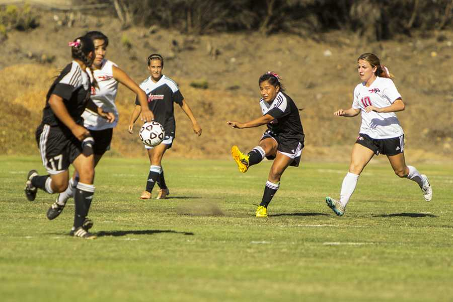 After a grueling battle over the ball City College freshman defender Stephanie Merida (center) kicks the ball to her offensive teammates during a home game against Palomar College on Oct. 3. Photo credit: Celia Jimenez