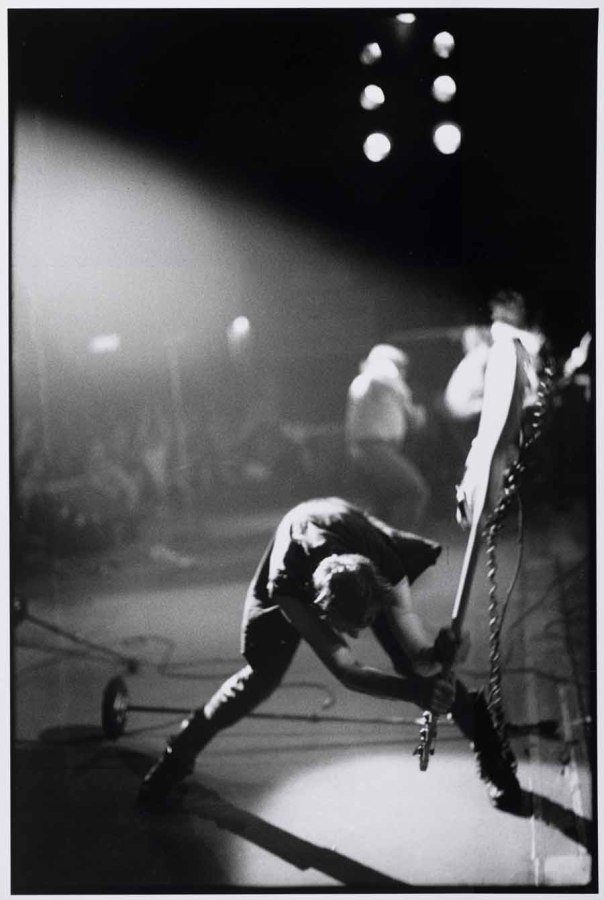 The Clash bassist Paul Simonon smashing his bass during a 1979 New York City concert at The Palladium. Photo by Pennie Smith.