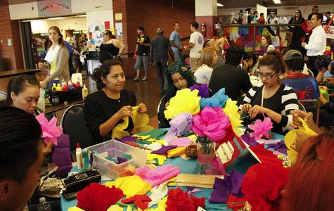 Students create crepe paper flowers to adorn Dia de los Muertos altars during the Oct. 30 event in the cafeteria. Photo credit: Celia Jimenez
