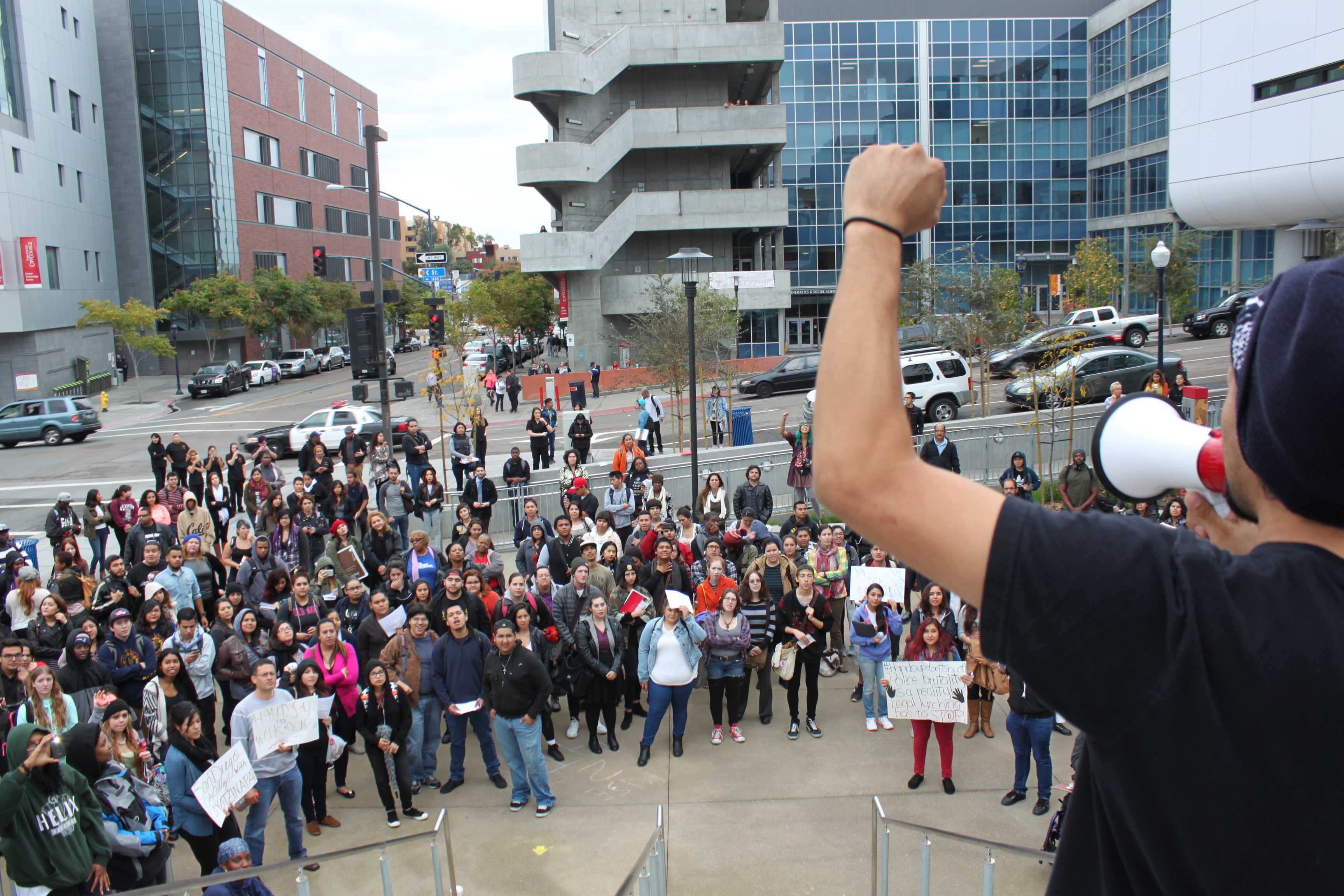 """Student and Students in Power member Tony Perez raises his fist, leading the crowd that gathered in the BT Plaza in a chant of """"We won't take it anymore,"""" referring to recent officer-involved deaths that have and haven't made national news. Photo credit: Miguel Cid"""