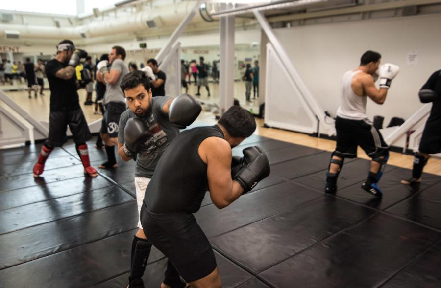 Mixed Martial Arts Club founders Roman Sanchez and Samuel Castorena work punching combination drills during a kickboxing class in the P building. Photo credit: Joe Kendall