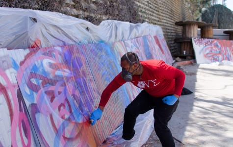"Chor Boogie works on his latest installment ""Bloom Bash"" for the San Diego Museum of Art. He repeatedly spray paints a blend of floral colors onto several large canvases on April 7. Photo credit: Richard Lomibao"