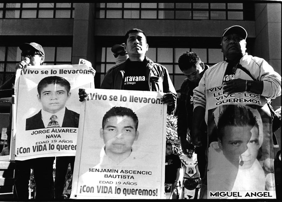 The family members of missing 43 Ayotzinapa students Jorge Alvarez Nava, Benjamin Ascencio Bautista and Miguel Angel Mendoza speak to listeners circling around the small stone stage. Photo credit: Mark Elliott