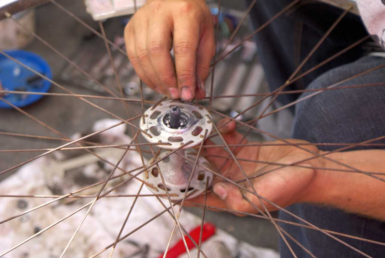 A visitor at the Bikes del Pueblo tent of the City Heights Farmers Market changes the bearings in the axle of a wheel from his bike with help and guidance from volunteers on April 18. Photo credit: Torrey Spoerer