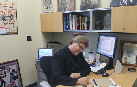 New KSDS Station Manager Ken Poston takes notes and fills out paperwork as he sits in his art-adorned office in the L building on Sept. 14, completing just one of many duties he has as the station's new manager. Photo credit: Katherine Salindayao-White