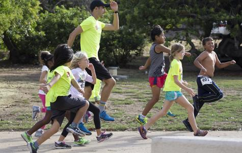 Marco Anzures, the new coach for the women's cross counrty team, warms up with second-recess kids before the Dirt Doggies 2K Watermelon Run on Oct. 3 at Morley Field. Photo by  Celia Jimenez