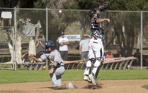 Sophomore infielder Alex Emerick (left) and freshman catcher Wyatt Logan (right)  battle to get first to the home plate. Emerick hits first and scores the sixth run for the Olympians during the ninth inning at Morley Field on Feb. 27.  Photo  credit: Celia Jimenez