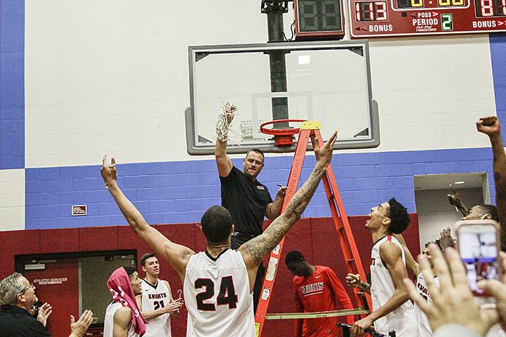 Coach Mitch Charles celebrates as the Knights are in the state quarter-finals on March 4 at Harry West Gym.