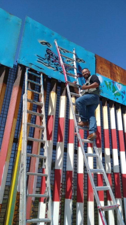 Artist, Enrique Chiu collaborates with the community and artists from around the world in painting on the border wall, 2017.