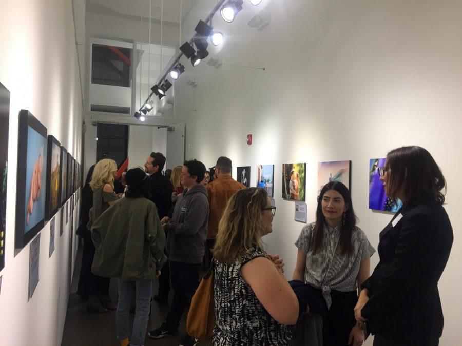 Guests viewing and speaking with local professional women photographers at Luxe Gallery. opening reception, Women in Photography Visual Voices. Feb. 9.