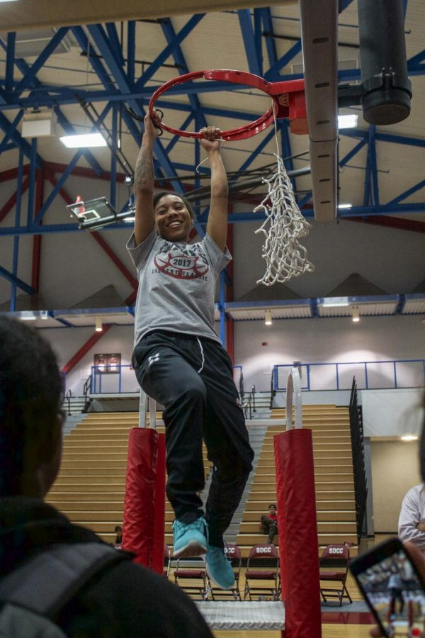 Lady Knights sophomore point guard, E'maniee Powell #21, slam dunks a free-body throw as the team celebrates the cutting of the net as they become the 2018 PCAC South Champions