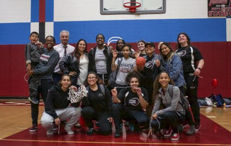 City College's Women's Basketball team, pose for a team picture behind the basketball net they cut in honor of their sophomore night and season.