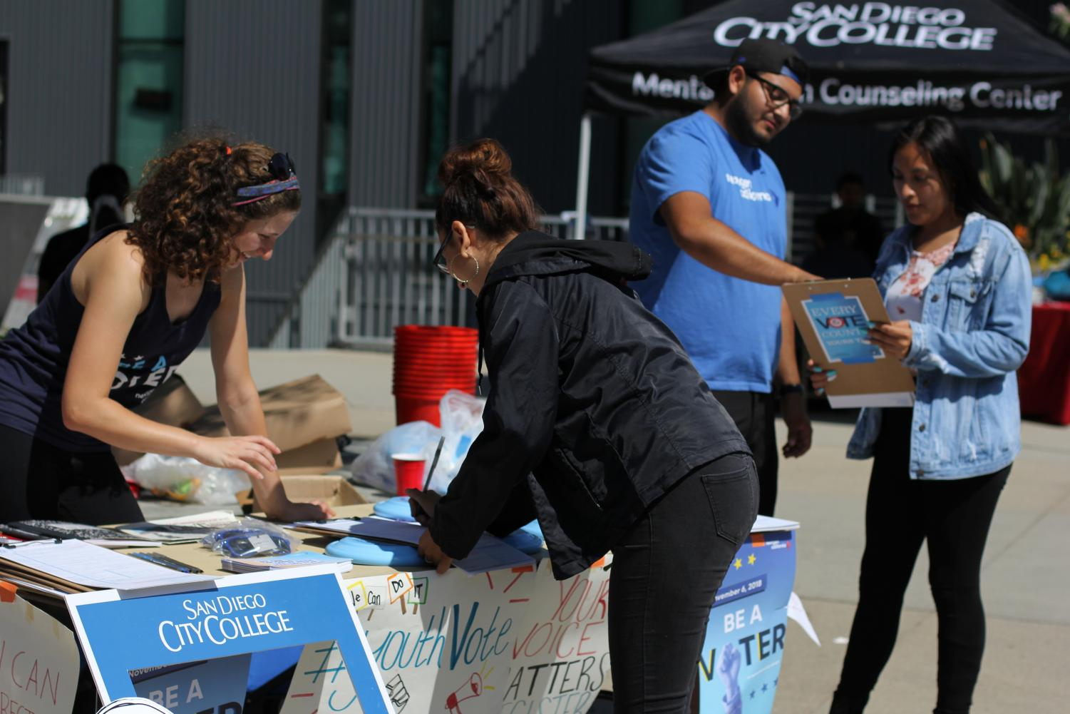 Juan Andres Villa (in blue, with hat)  and Jessica Cohen (in black tank) of Nextgen were on campus helping register students to vote on Sept. 25 in the AH quad. Photo by Nadia Mishkin.