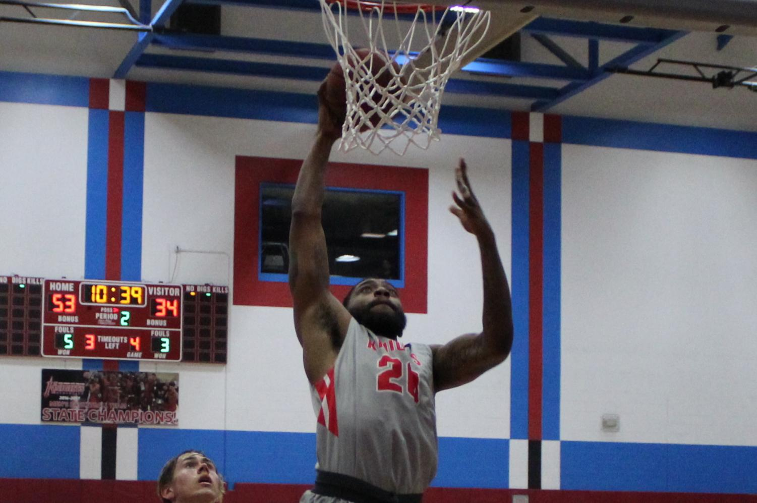Dantrell Anderson goes up high to dunk the ball in the Knights' 75-49 win over Grossmont. By Jonny Rico/City Times