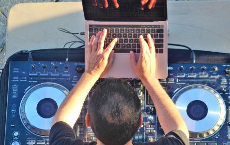 Dr. Rob mixing songs at DJ table