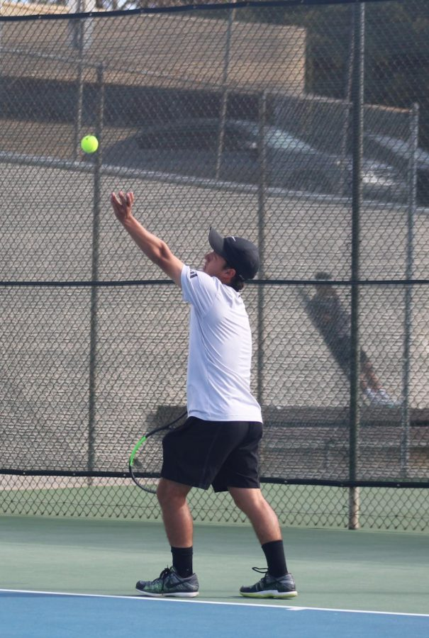 Colin Palmer serving at a tennis match