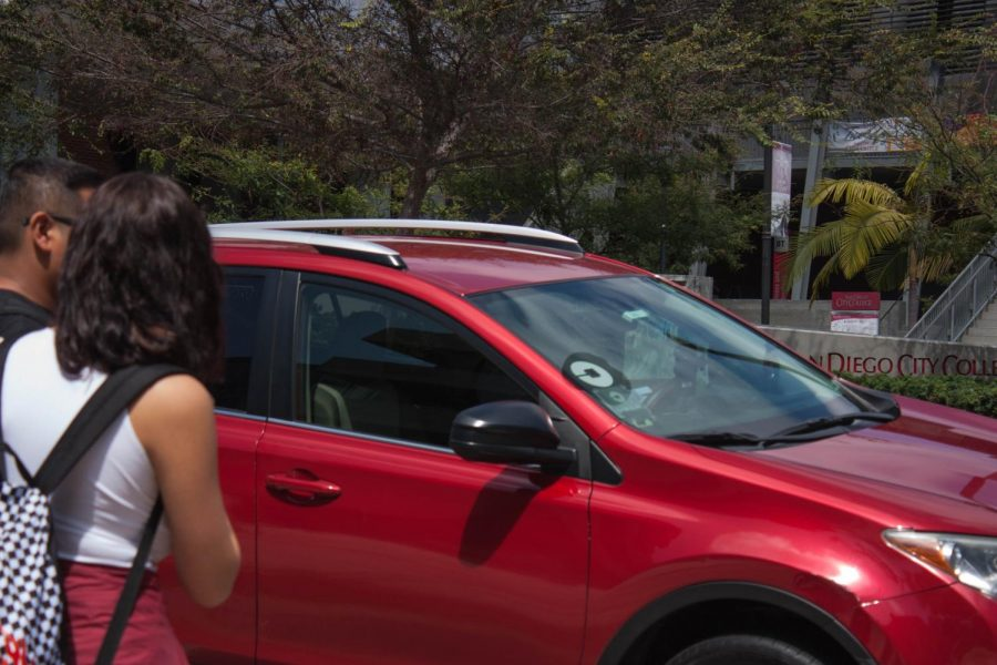 San Diego City College Students stand in front of an Uber vehicle on campus.