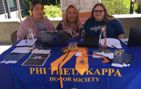 Members of the club Phi Theta Kappa sit behind their booth at club rush.