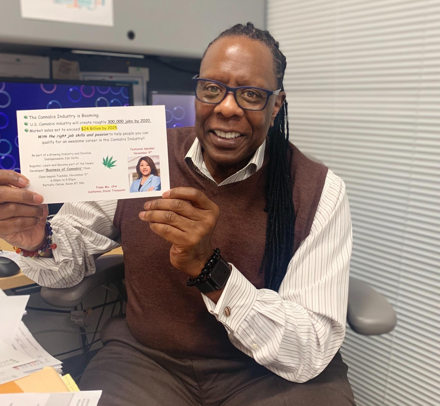 Dr. Leroy Brady displays a flier for the new Business of Cannabis course. Photo by Jade Benn.