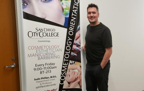 Michael eceltka stands in front of an ad for the City College cosmo program.