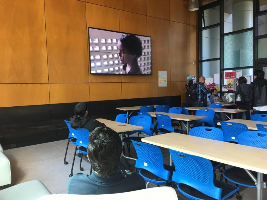 The film Pelo Malo plays on a screen in the Subir Center