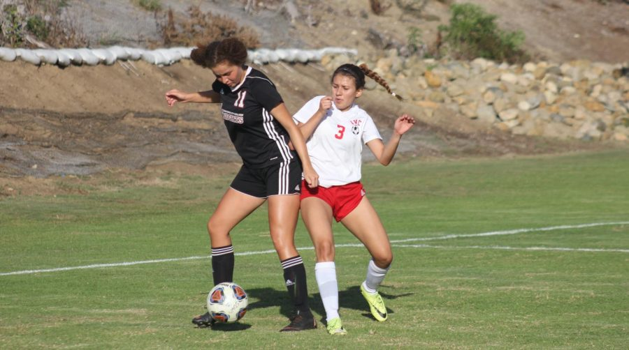 A City College player defends the soccerball against an Imperial Valley College opponent during a match