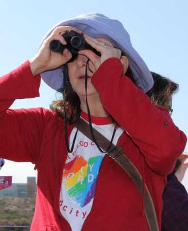 Lisa Chaddock Looks through binoculars during a nature walk.