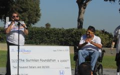 A woman presents Humberto Gurmilan with a big check.