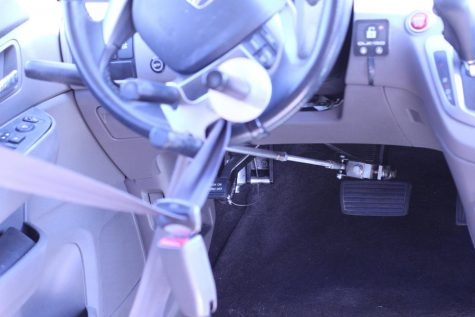 The hand controls of a vehicle adapted to be driven by a person using a wheelchair.