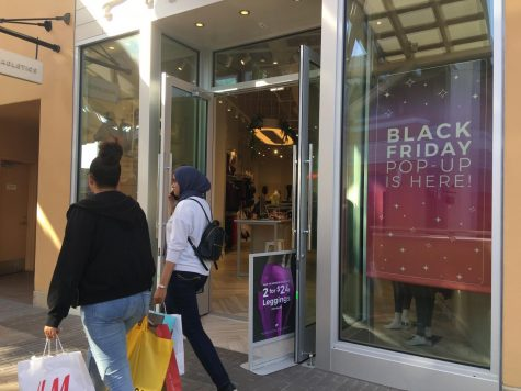 Women at a mall walk aoutside of a store advertising a black friday sale.