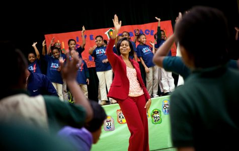 First Lady Michelle Obama in a r4ed suit dancing with her eyes close with a group of girls in blue shirts.