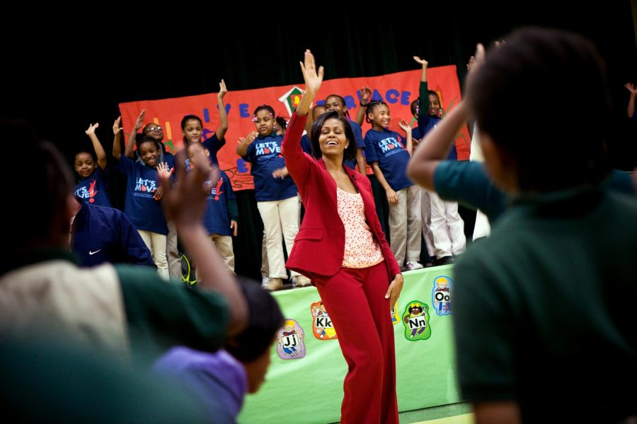 First+Lady+Michelle+Obama+in+a+r4ed+suit+dancing+with+her+eyes+close+with+a+group+of+girls+in+blue+shirts.