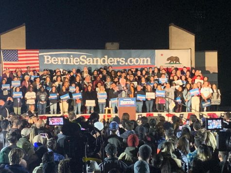 Bernie Sanders with a crowd in a podium at San Ysidro High School.