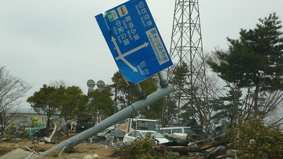Fallen sign after the Tsunami at Japan, destruction in the background.