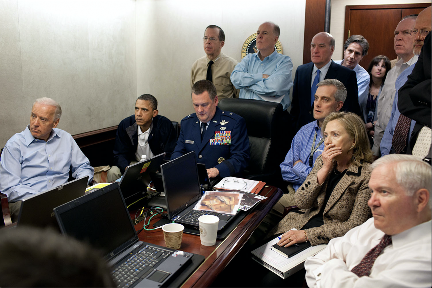 """President Barack Obama and Vice President Joe Biden, along with members of the national security team, receive an update on the mission against Osama bin Laden in the Situation Room of the White House, May 1, 2011. Seated, from left, are: Brigadier General Marshall B. """"Brad"""" Webb, Assistant Commanding General, Joint Special Operations Command; Deputy National Security Advisor Denis McDonough; Secretary of State Hillary Rodham Clinton; and Secretary of Defense Robert Gates. Standing, from left, are: Admiral Mike Mullen, Chairman of the Joint Chiefs of Staff; National Security Advisor Tom Donilon; Chief of Staff Bill Daley; Tony Blinken, National Security Advisor to the Vice President; Audrey Tomason Director for Counterterrorism; John Brennan, Assistant to the President for Homeland Security and Counterterrorism; and Director of National Intelligence James Clapper. Please note: a classified document seen in this photograph has been obscured. (Official White House Photo by Pete Souza)   This official White House photograph is being made available only for publication by news organizations and/or for personal use printing by the subject(s) of the photograph. The photograph may not be manipulated in any way and may not be used in commercial or political materials, advertisements, emails, products, promotions that in any way suggests approval or endorsement of the President, the First Family, or the White House."""