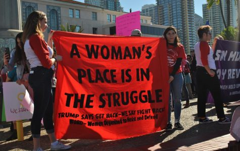 Two women holding a red sign that says,