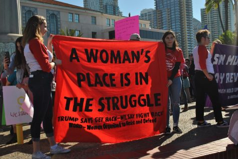 "Two women holding a red sign that says, ""A woman's place is in the struggle."" Other women in the back."