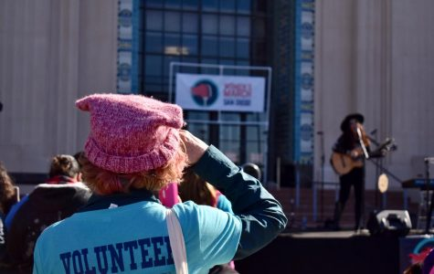 Volunteer of the Women's March with a blue shirt than the representative pink hat of the Women's March, looking at the stage.
