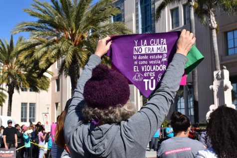 "Women holding a purple sign. that reads ""The fault was not mine nor where I was, nor what I was wearing"" in Spanish."