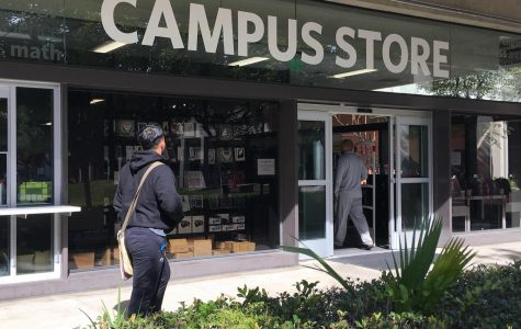 Front of the Campus Store, with one male student entering, and another male student walking by