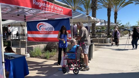 A senior couple in front of a registrar of voter tent.